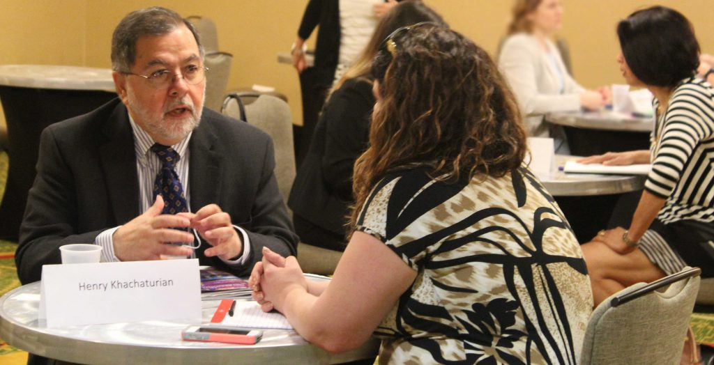 NIH staff member Dr. Henry Khachaturian meets with an attendee of the NIH Regional seminar at an 1:1 session